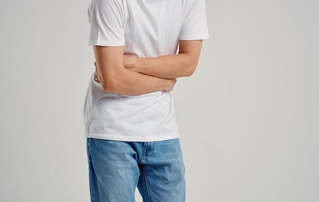 Homem de camiseta branca e jeans, tocando seu estômago com as mãos, dor de estômago, indigestão.