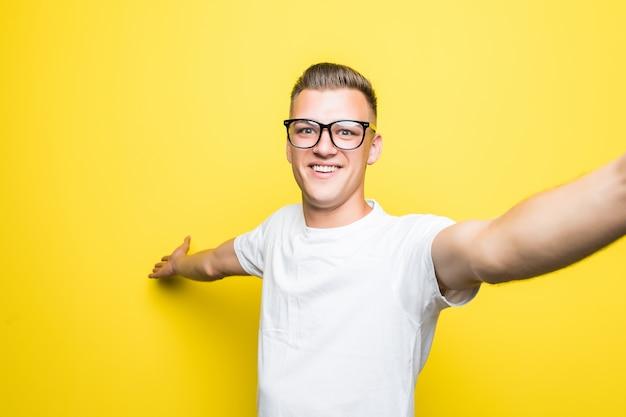 Homem de camiseta branca e óculos faz algo em seu telefone e tira fotos de selfie isoladas em amarelo