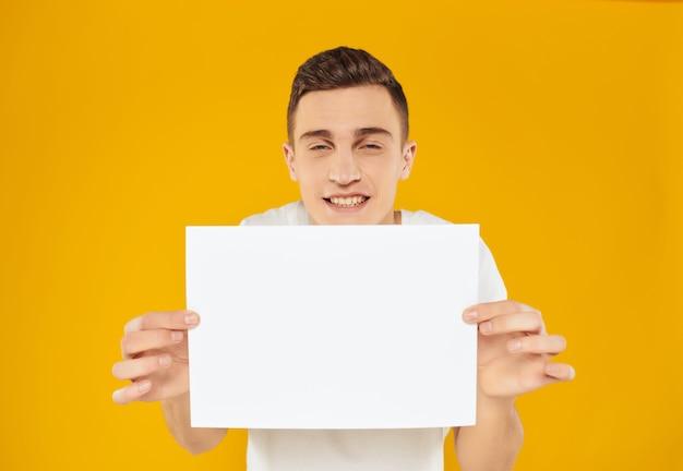 Homem de camiseta branca, folha de papel, anúncio, apresentação, fundo amarelo