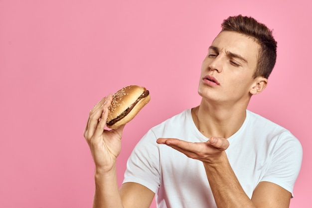 Homem de camiseta branca hambúrguer estilo de vida rosa fundo comendo