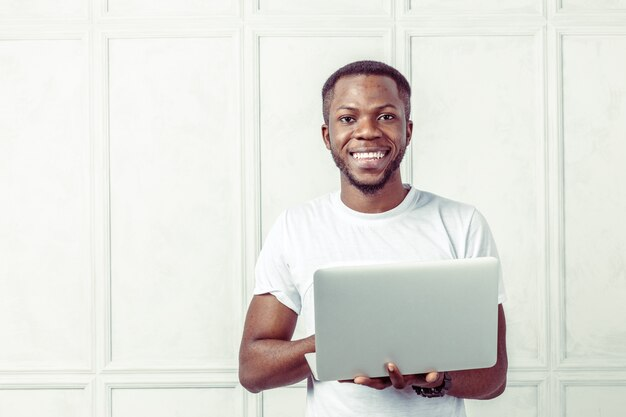 Homem de camiseta branca, segurando um laptop