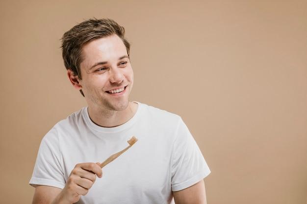 Homem de camiseta branca segurando uma escova de dentes de madeira