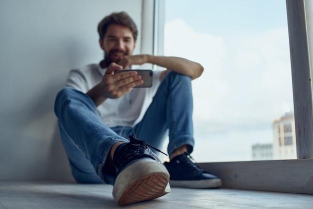 Homem de camiseta branca sentado na sala com fones de ouvido estilo de vida. foto de alta qualidade