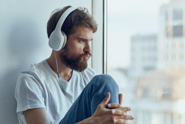 Homem de camiseta branca sentado no parapeito da janela com fones de ouvido, estilo de vida fones de ouvido