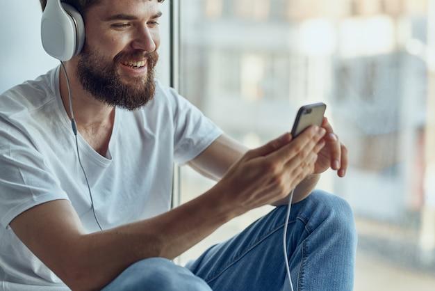 Homem de camiseta branca sentado no parapeito da janela em fones de ouvido em fones de ouvido. foto de alta qualidade