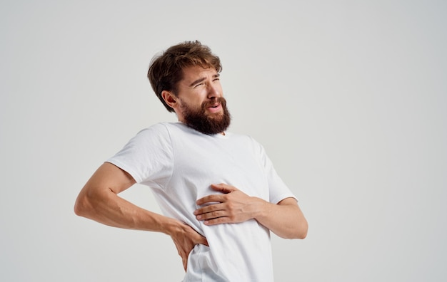 Homem de camiseta branca sofrendo de dor