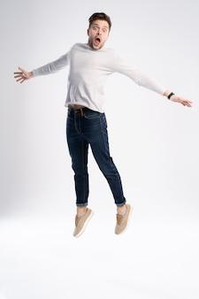 Homem de camiseta casual e jeans, pulando isolado sobre fundo branco.