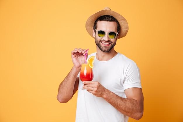 Homem de camiseta mostrando saboroso cocktail