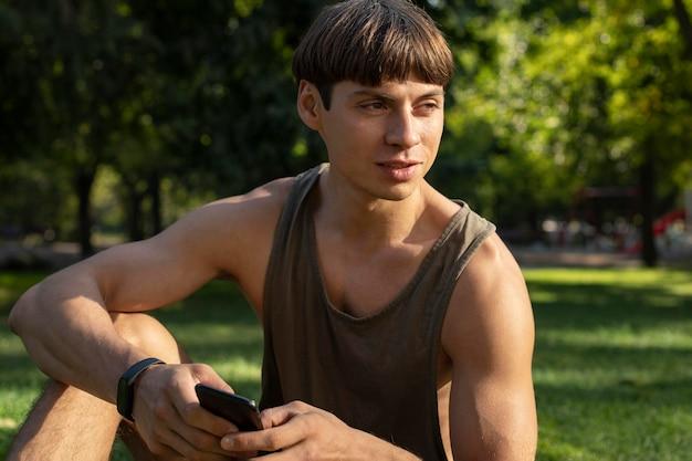 Homem de camiseta sem mangas segurando smartphone ao ar livre
