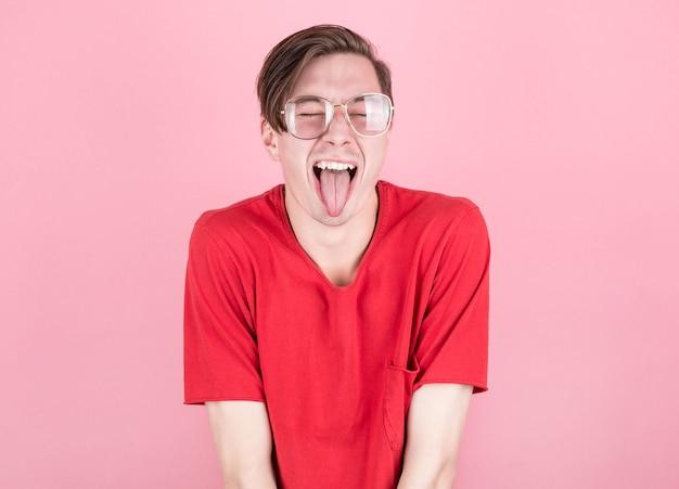 Homem de camiseta vermelha e óculos mostrando a língua com os olhos fechados em um fundo rosa