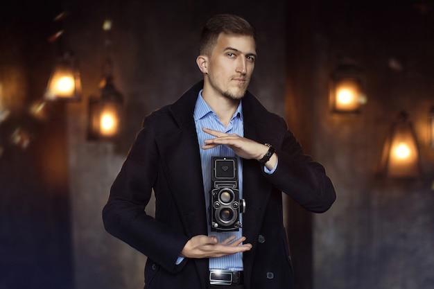 Homem de capa de chuva e camisa nas mãos levita câmera vintage