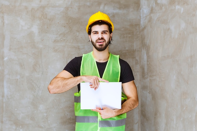 Homem de capacete amarelo e equipamento segurando relatórios de projeto