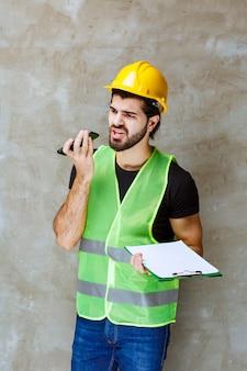 Homem de capacete amarelo e equipamento segurando um plano de projeto e falando ao telefone