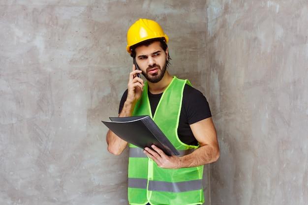 Homem de capacete amarelo e equipamento, segurando uma pasta de relatório e falando ao telefone