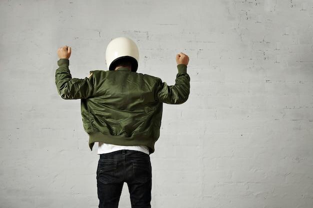 Homem de capacete branco de motocicleta e retrato de jaqueta de piloto verde na parte de trás com os dois punhos no ar com gesto de shaka na parede branca.