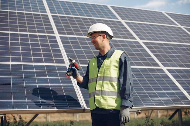 Homem de capacete branco perto de um painel solar