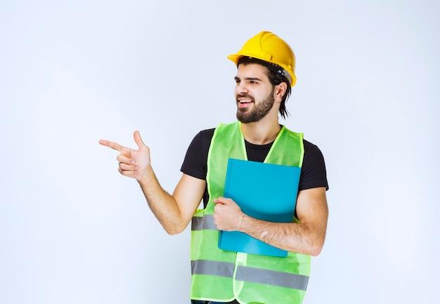 Homem de capacete segurando uma pasta azul e apontando alguém à esquerda.
