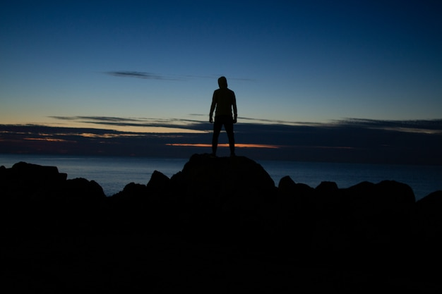 Homem de capuz em pé sobre as rochas no fundo do mar no entardecer