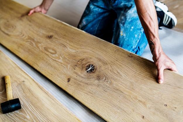 Homem de carpinteiro instalar o piso de madeira