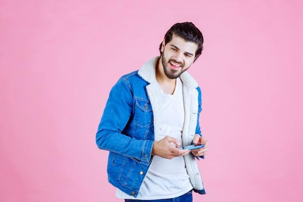 Homem de casaco azul escrevendo mensagem ou comentando ao telefone.