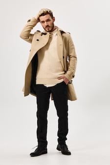 Homem de casaco bege com a mão atrás da cabeça