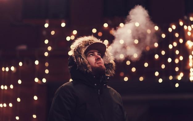 Homem de casaco fumando um cigarro no contexto da cidade à noite