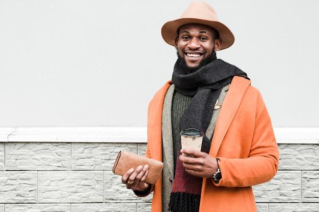 Homem de casaco laranja, segurando uma xícara de café e sua carteira