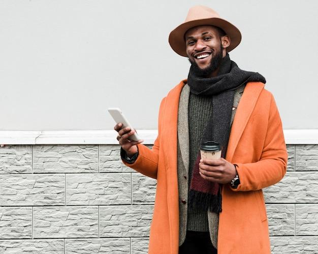 Homem de casaco laranja, segurando uma xícara de café e um telefone