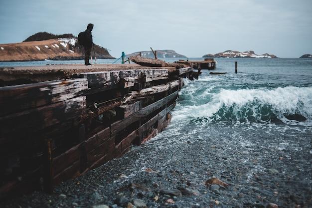 Homem de casaco preto de pé na doca de madeira marrom durante o dia