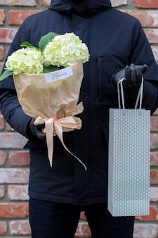 Homem de casaco preto segurando flores e bolsa