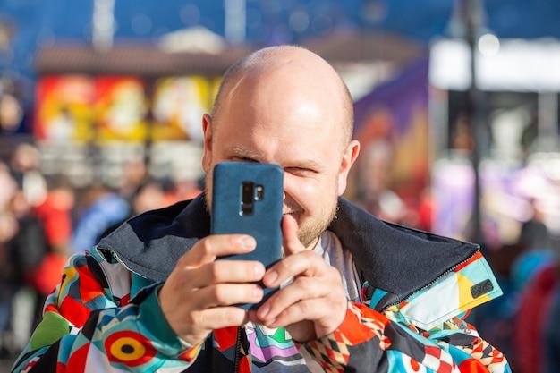 Homem de casaco tira fotos da paisagem no telefone