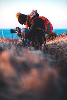 Homem de casaco vermelho e preto, segurando a câmera no campo de grama marrom durante o pôr do sol