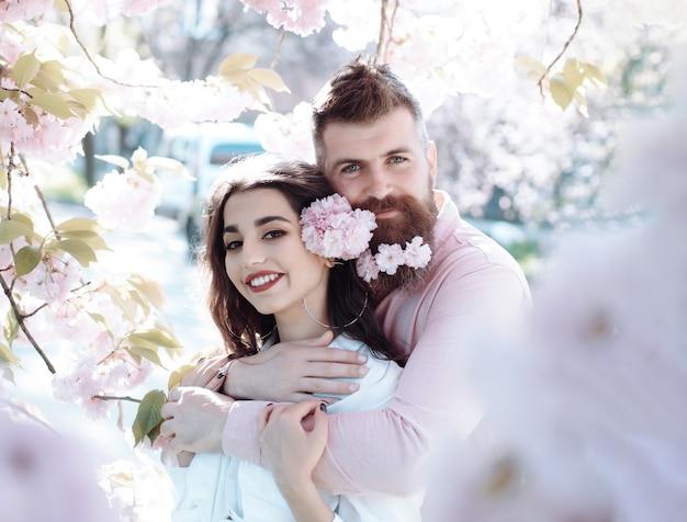 Homem de casal de primavera abraçando uma menina sorridente cercada por pétalas de rosa de árvore florescendo casal feliz em um encontro romântico linda menina com flores e homem alegre com flor na barba no jardim