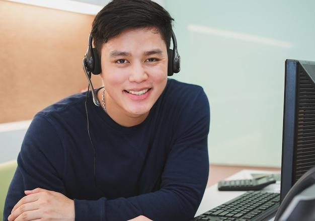 Homem de centro de chamada asiática com fone de ouvido no escritório desktop
