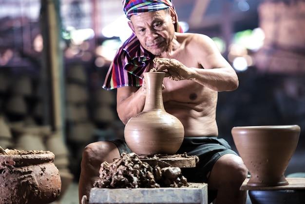 Homem de cerâmica com seu produto, mãos feitas.