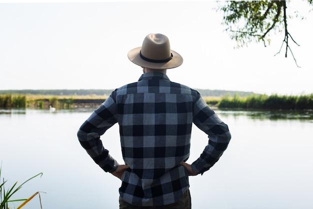 Homem de chapéu e camisa xadrez admira a paisagem à beira do rio.
