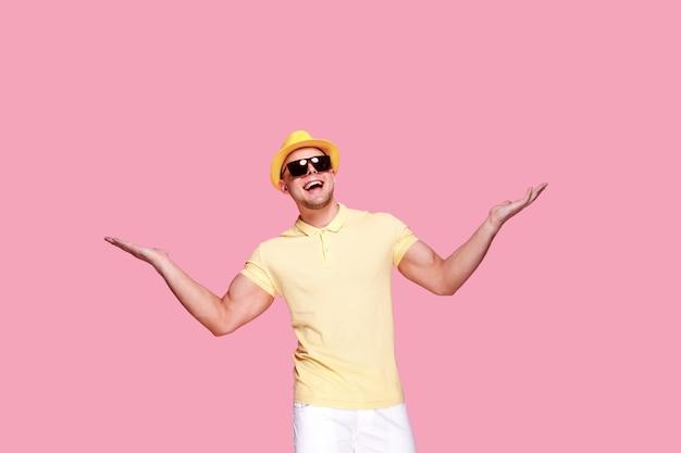 Homem de chapéu e óculos de sol com as mãos para cima