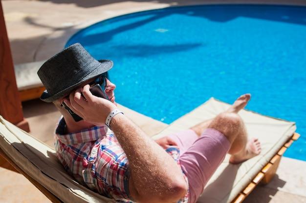 Homem de chapéu sentado à beira da piscina e falando ao telefone