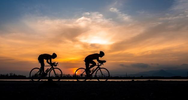 Homem de ciclista de bicicleta de estrada silhueta dois andar de bicicleta pela manhã.