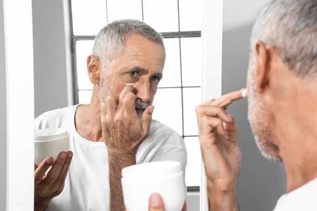 Homem de close-up aplicando creme facial