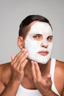 Homem de close-up aplicando máscara facial