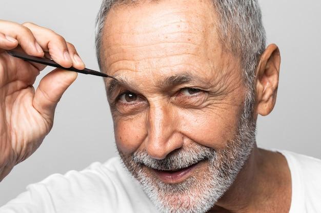 Homem de close-up arrancando a sobrancelha
