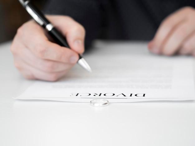 Homem de close-up, assinando contrato de divórcio