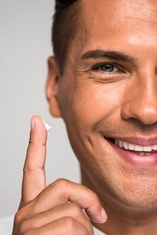 Homem de close-up com creme no dedo