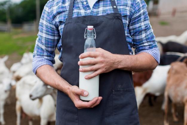 Homem de close-up com garrafa de leite de cabra
