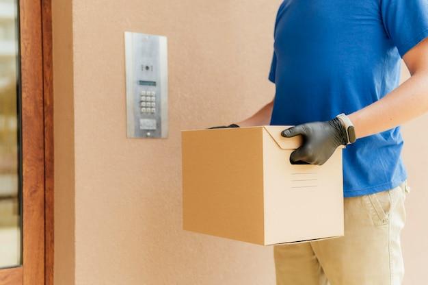 Homem de close-up com luvas segurando uma caixa