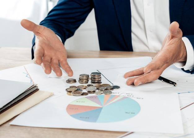 Homem de close-up com moedas e estatísticas