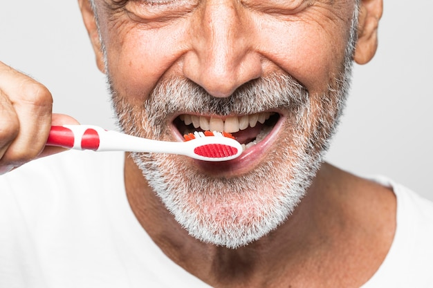 Homem de close-up escovando os dentes