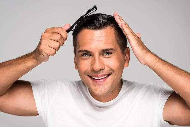 Homem de close-up penteando o cabelo