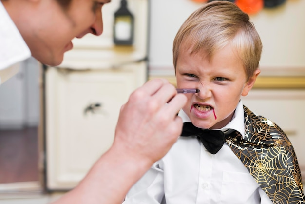 Homem de close-up pintando rosto de criança